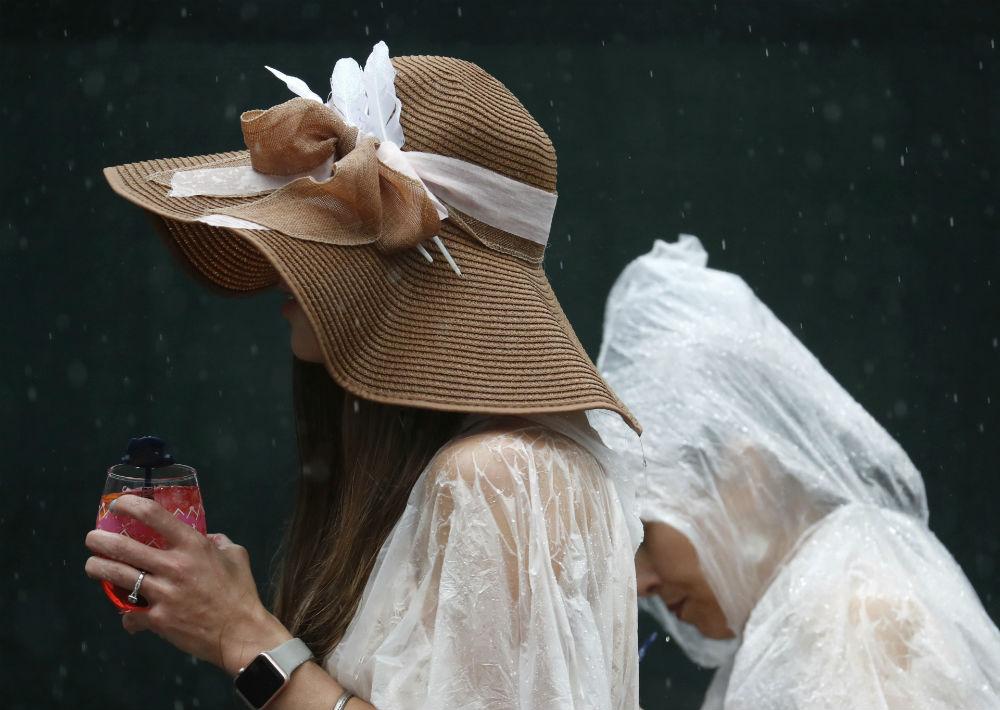 Una mujer camina luciendo una pamela con gran lazo, mientras que otra se protege de la lluvia usando una bolsa plástica sobre su cabeza. (Foto: AP/John Minchillo)