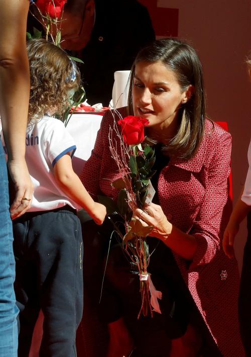 Letizia recibe una rosa de manos de una niña durante la cuestación. (Foto: EFE)