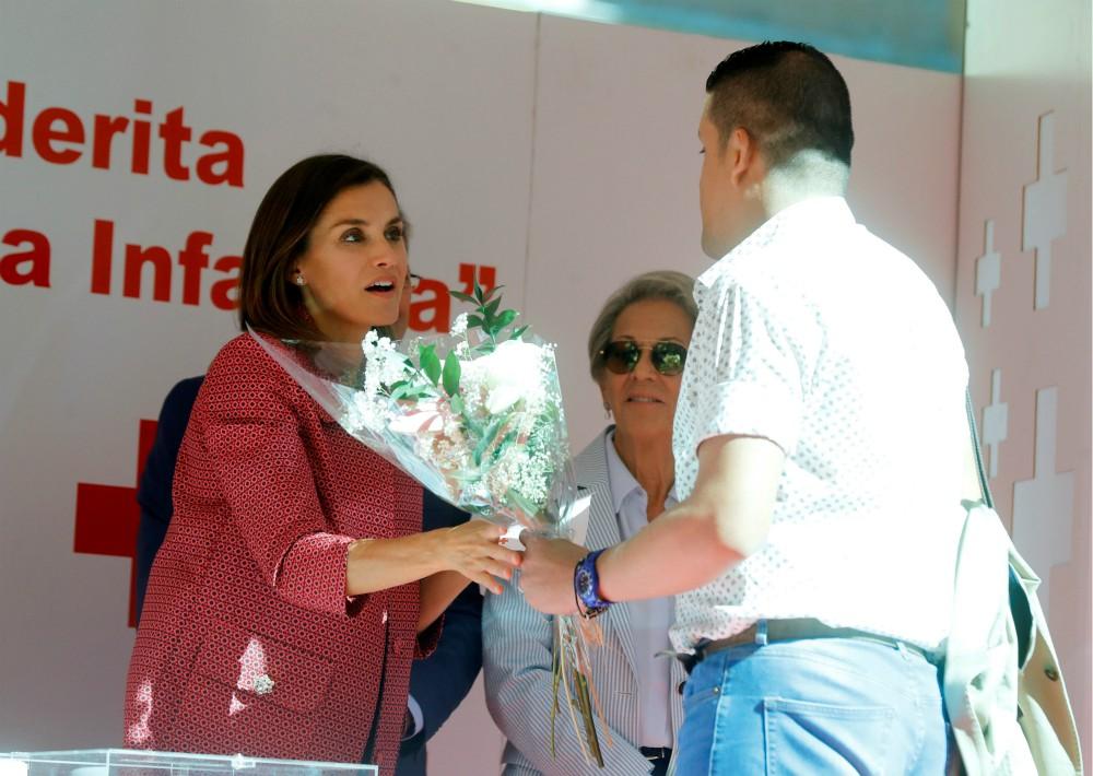 La reina recibe un ramo de flores mientras preside una mesa de cuestación. (Foto: EFE)