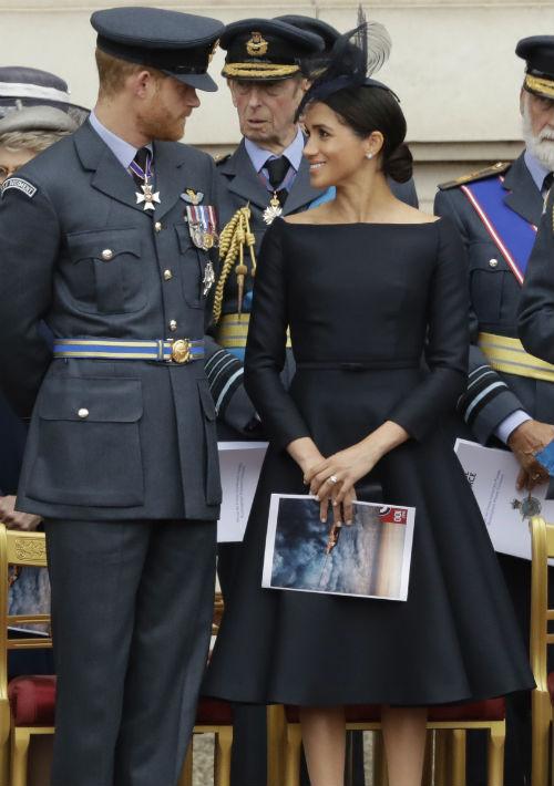 """En su primer compromiso del día, Meghan volvió a presentarse en el balcón del palacio de Buckingham junto a la familia real, esta vez con un vestido negro con escote barco y falda ancha, diseño de la casa de moda Dior. El complemento de este """"look"""" que a muchos recordó a la legendaria actriz Audrey Hepburn, fue un sombrero Stephen Jones, aretes de Cartier y zapatos cerrados en tono """"unde"""". (AP)"""