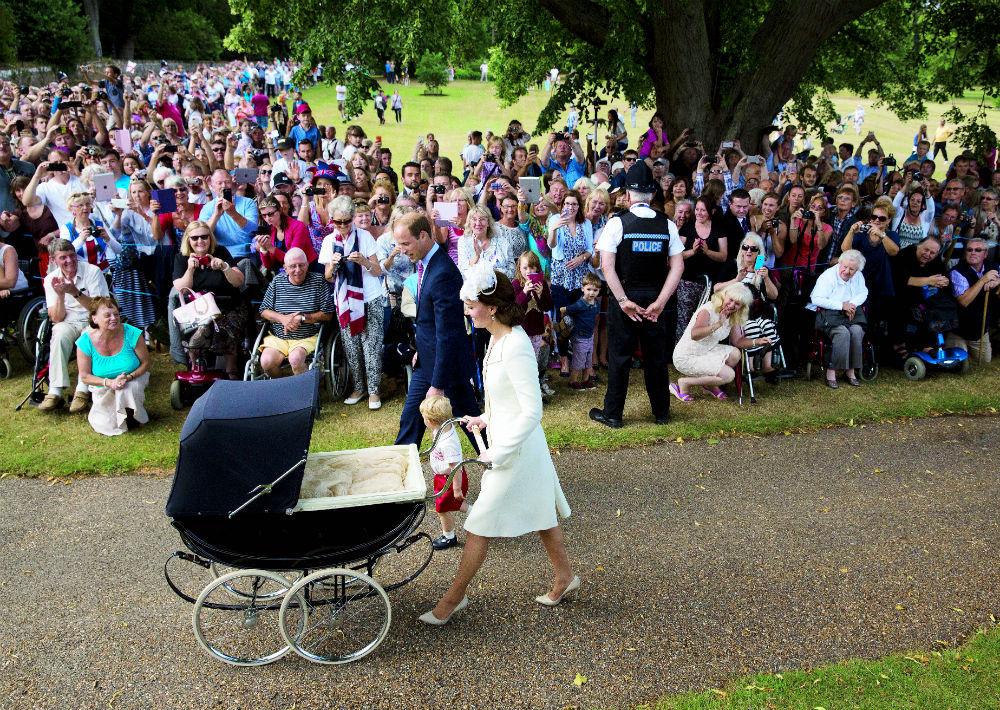 El príncipe William, su esposa Kate, el príncipe George y la princesa Charlotte caminan hacia la iglesia de Santa María Magdalena de Sandringham donde la pequeña será bautizada. A ambos lados de la calle, el pueblo observa el evento. (AP)