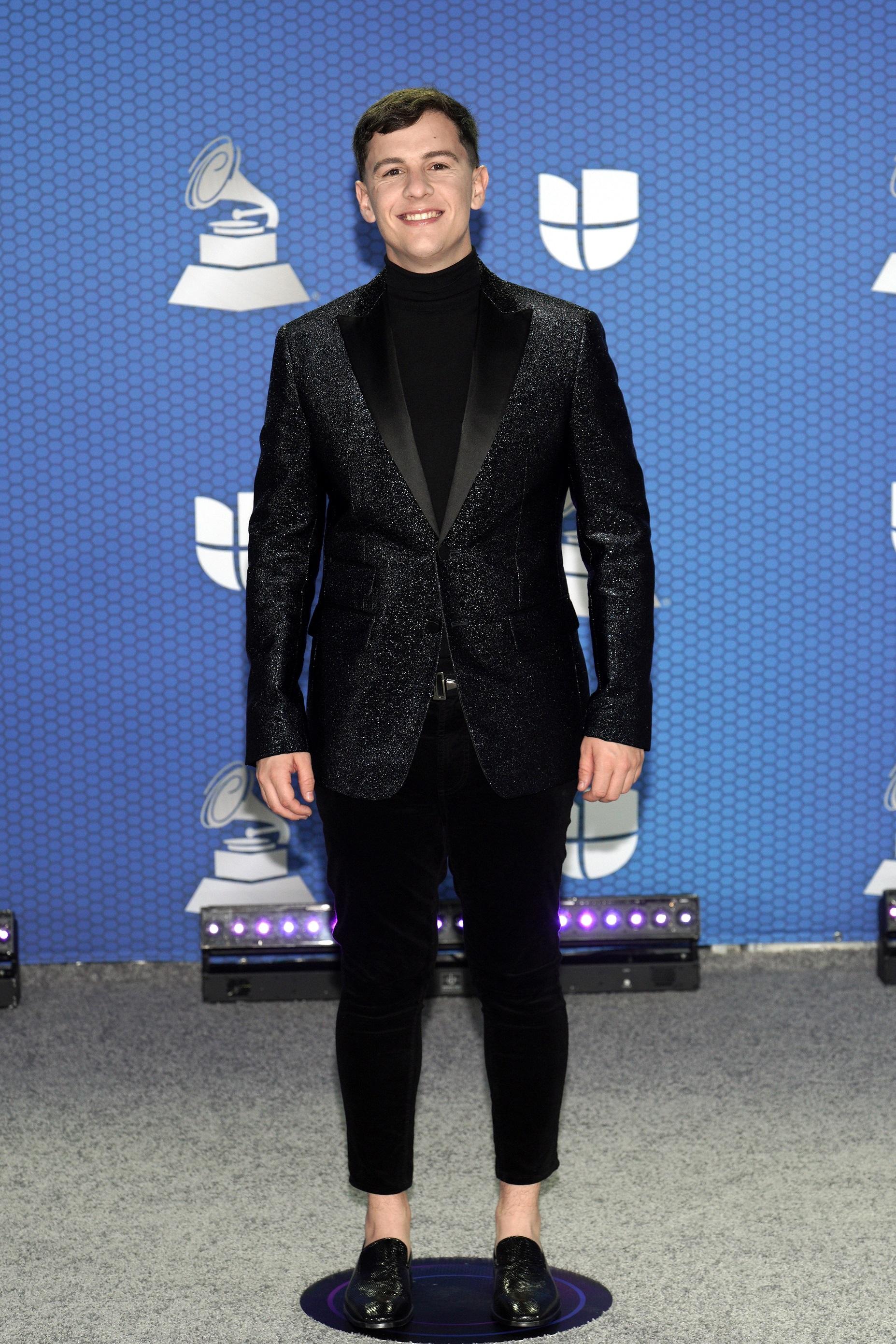 El puertorriqueño Guaynaa decidió lucir sobrio y elegante para la ocasión con camisa de cuello alto, pantalón y chaqueta negra con brillo. (Foto: Suministrada/ Univisión)