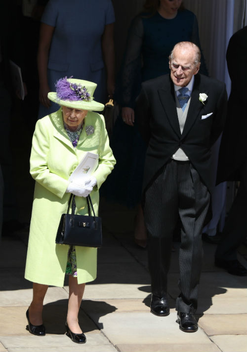 La reina Elizabeth II vistió un conjunto en tonos claros de verde con acentos púrpura. (AP)