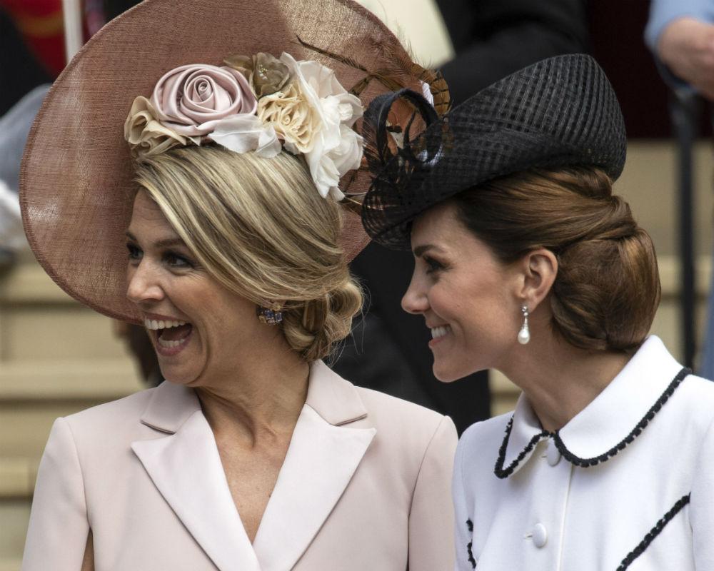 La reina de origen argentino Máxima Zorreguieta optó por un vestido rosa con capa y cinturón del mismo color. Para la ceremonia oficial no lució tocado ni accesorios en el cabello, pero al momento de salir al desfile sí lo hizo. (AP)
