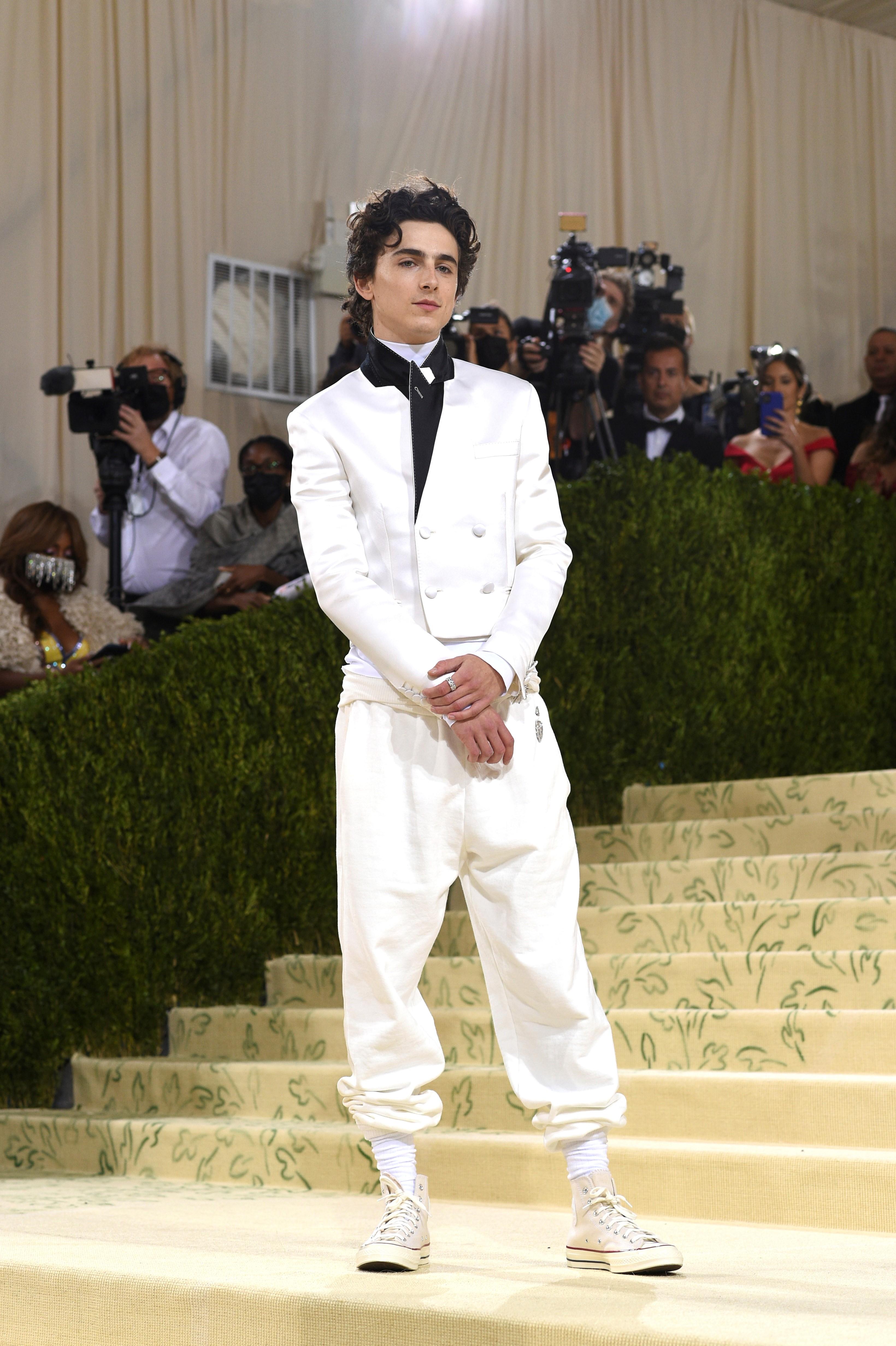 El actor Timothee Chalamet optó po un look del diseñador francés Haider Ackermann en blanco formado por una chaqueta de traje corta y pantalones jogger, que combinó con zapatillas Converse. (AP)