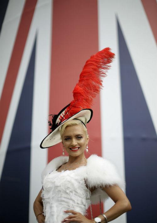 La invitada lleva puesto un sombrero blanco, bordado con una cinta negra, con una pluma roja que sobresale del lado izquierdo de su accesorio. (Foto: AP)