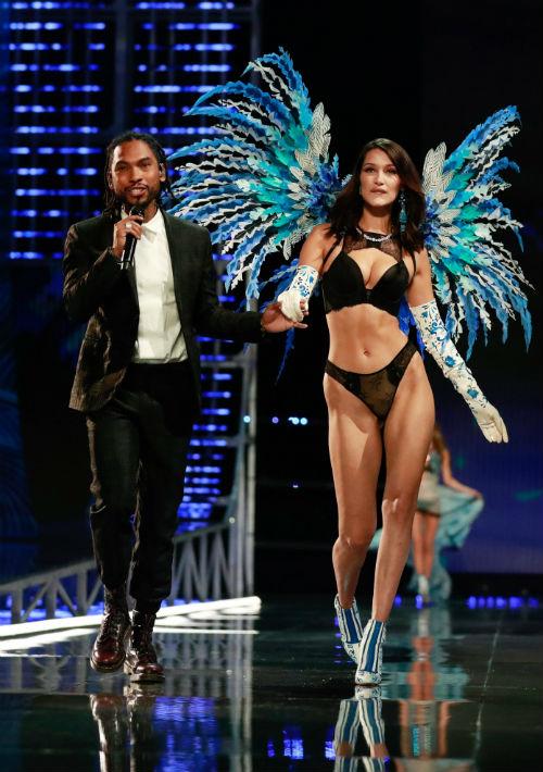 La modelo estadounidense Bella Hadid presenta una creación de Victoria's Secret junto al cantante estadounidense Miguel, durante el desfile en el que la gran ausente fue su hermana Gigi. (EFE/ Sherwin)