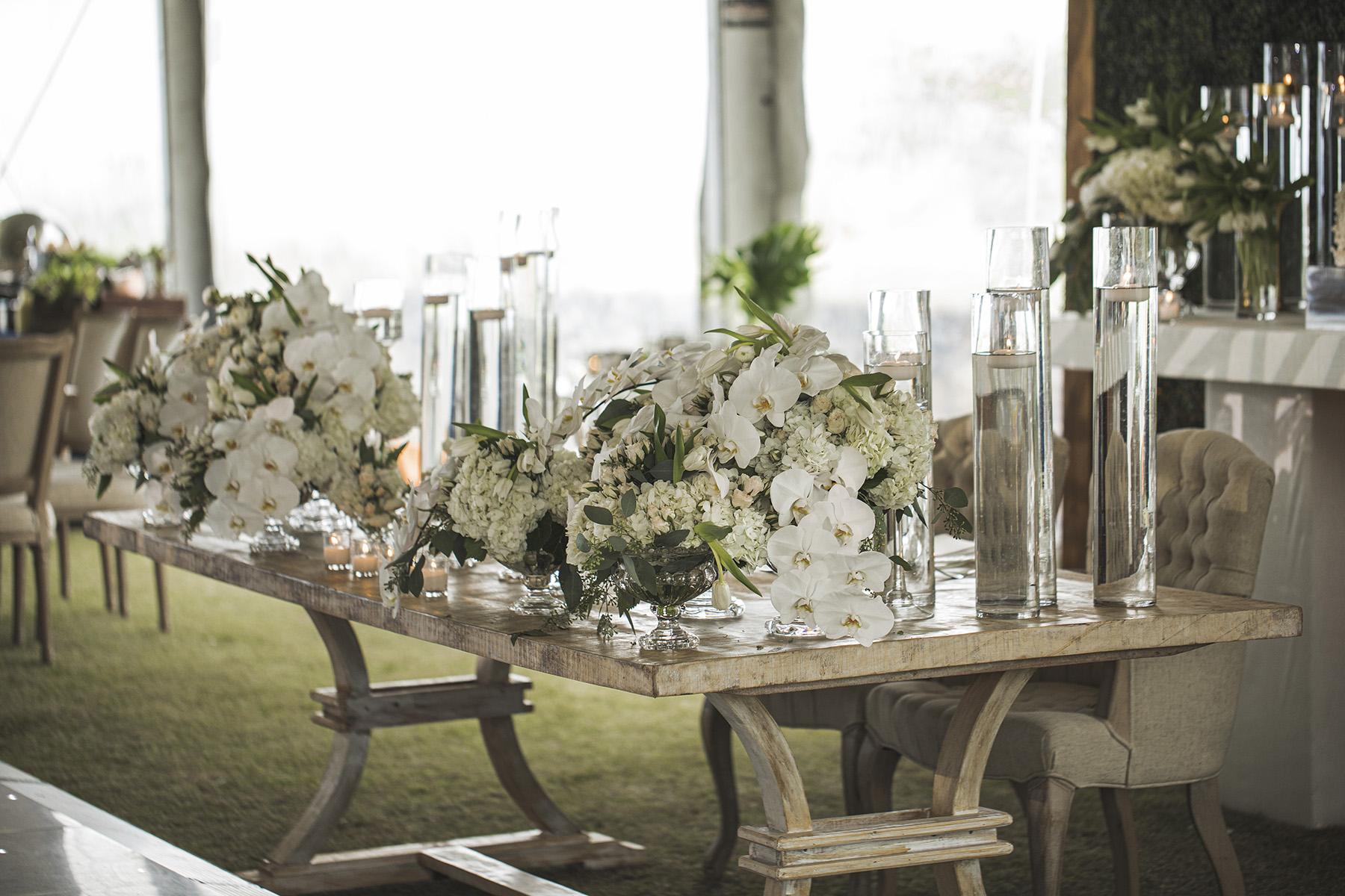 La decoración con maderas rústicas claras, orquídeas, hortensias blancas y follaje, fue obra de Luciano Designers. Fotografía Wedding Mafia.