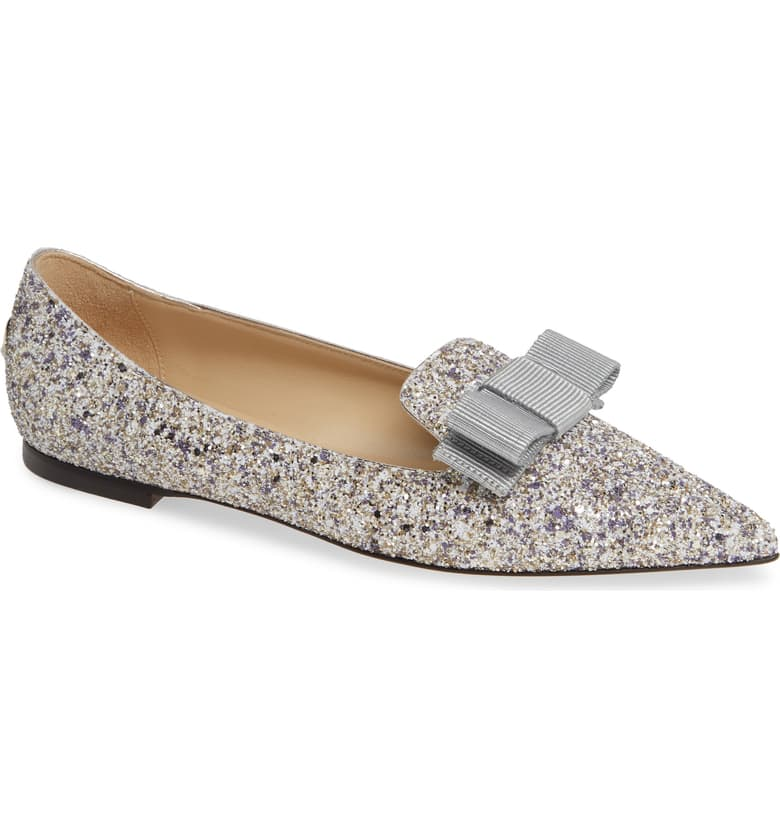 """Jasmine se caracteriza por el uso de babuchas, un calzado ligero, sin tacón y con punta alargada forrada en cuero, muy utilizada por los musulmanes. Aunque en occidente no son fáciles de encontrar, sí puedes entrar en la onda de """"Aladdin"""" seleccionando un zapato """"flat"""" con puntera larga. En la foto, calzado Gala Bow Flat Jimmy Choo, disponible en Nordstrom. (Suministrada)"""