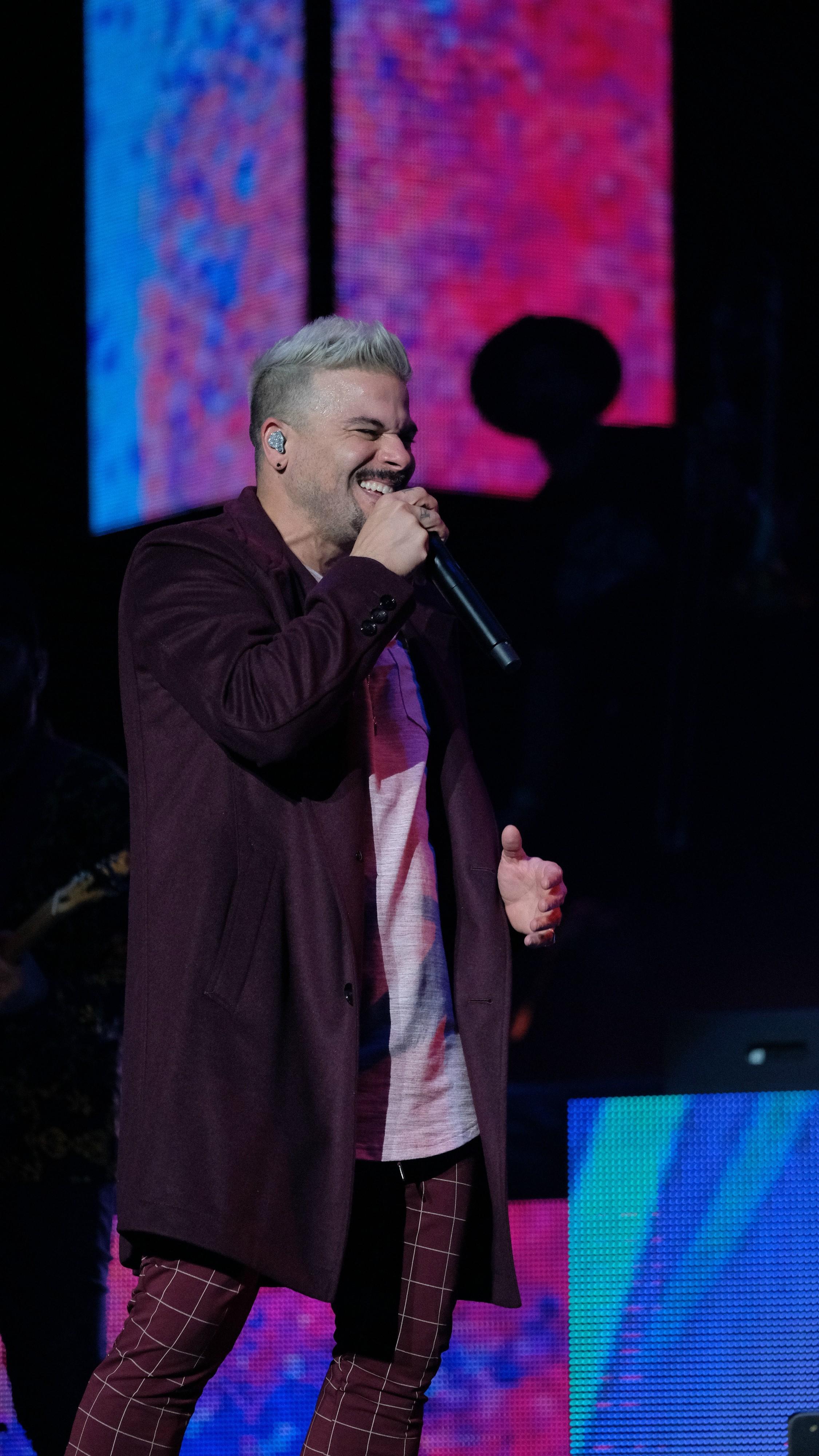 El nominado al Latin Grammy en la categoría de Canción del año lució una chaqueta larga y pantalón color vino con camiseta rosa. (Suministrada)