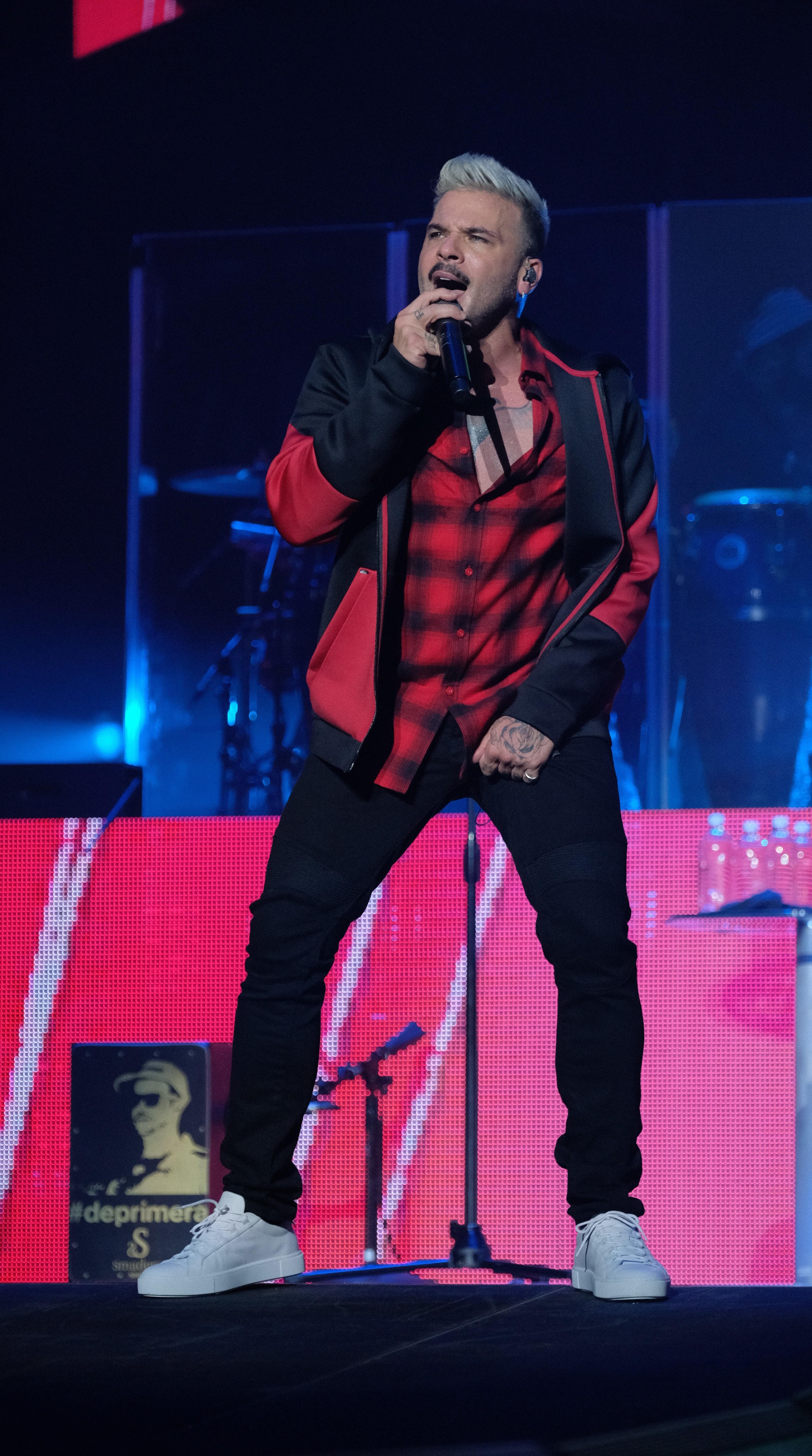 """Esta vez lució un conjunto de """"track jacket"""" en negro y rojo, camisa de cuadros en los mismos tonos y mahón negro. (Suministrada)"""