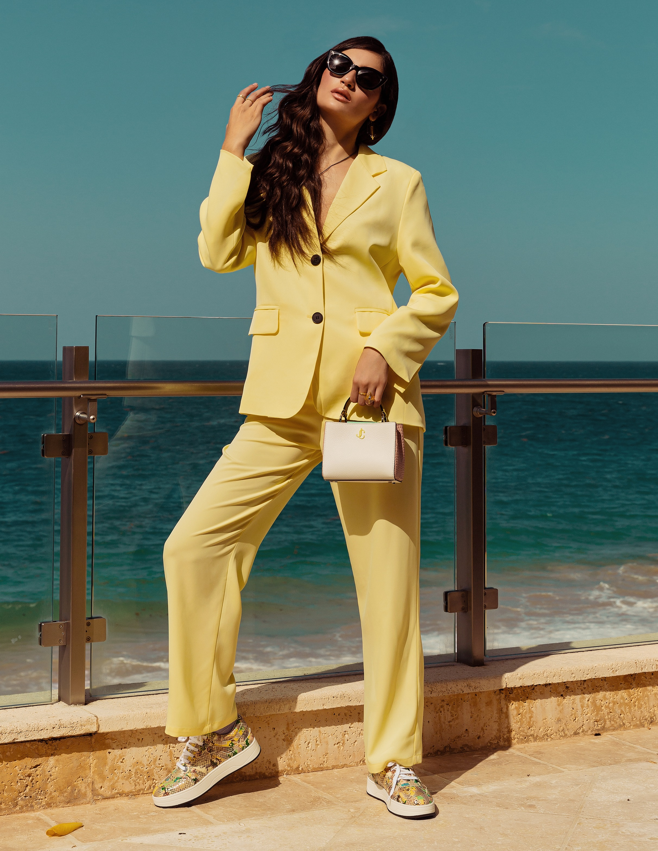 Suit amarillo, de Never Overdressed; calzado y bolso, de Jimmy Choo; joyería, de Reinhold Jewelers; y gafas Oliver's People, de Olivia's Boutique. (Foto: Nolan Rivera/ Especial para Magacín)