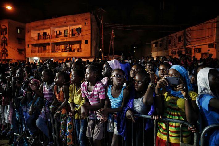 Jóvenes senegaleses ven un desfile al aire libre durante la Semana de la Moda de Dakar. (Prensa Asociada)