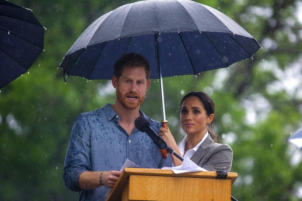 La imagen de Meghan Markle, cuyo embarazo se acaba de anunciar , cubriendo a su esposo con un paraguas se volvió viral en las redes sociales. (Foto: AP)