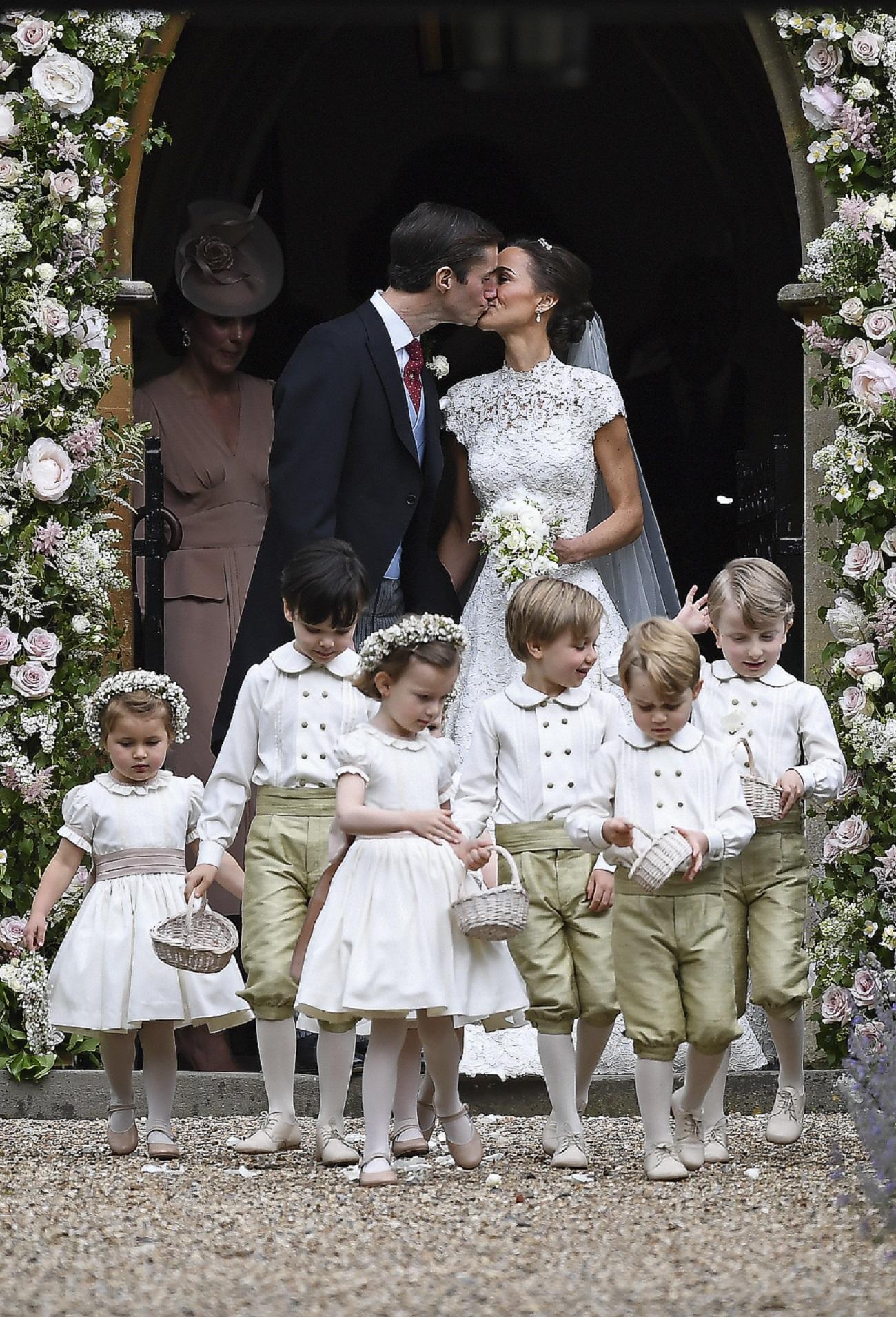 La pareja comparte su primer beso para las cámaras al salir de la capilla. (AP Photo/Kirsty Wigglesworth, Pool)