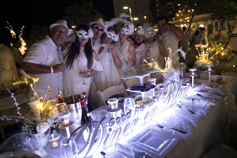 Grupo de invitados -las damas con máscaras de carnaval- lució su espacio con un gran centro de mesa que leía: Good Friends at Dîner en Blanc San Juan.