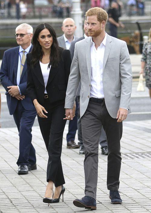 """A su llegada al Museo de Emigración Irlandesa, en Dublín, Markle llamó la atención con un conjunto de pantalón de pierna recta y chaqueta clásica en color negro y blusa blanca, de Givenchy. Lo acompañó con """"pumps"""" y cartera sobre también negros. (AP)"""