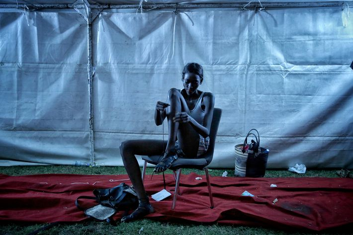 Una modelo ata las trenzas de sus sandalias al terminar su trabajo en la Semana de la Moda de Dakar. (Prensa Asociada)
