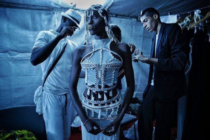 El diseñador Oumar Dicko, a la derecha, de Mali y Bélgica, viste a una modelo con una de sus creaciones durante la Semana de la Moda de Dakar, en la capital senegalesa. (Prensa Asociada)