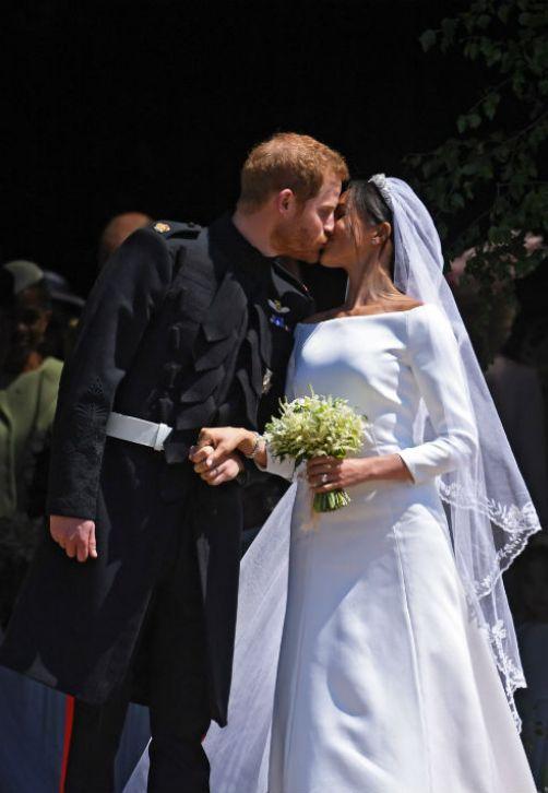 El príncipe Harry y su esposa Meghan Markle se dan el tan esperado beso a su salida de la capilla San Jorge en Windsor, luego de una emotiva ceremonia nupcial que duró una hora. (EFE)