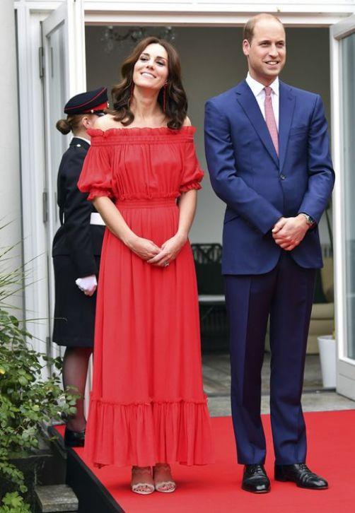 La duquesa de Cambridge luce un vestido off shoulder rojo de Alexander McQueen, en un garden party en honor al cumpleaños de la Reina en la residencia del embajador británico de Berlín. (Prensa Asociada)