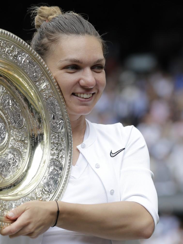La rumana Simona Halep posa con el trofeo después de derrotar con facilidad a Serena Williams en la final de mujeres de Wimbledon, en Londres. (AP Foto/Ben Curtis)
